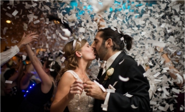 Magical Wedding Kiss Amidst White Confetti and Magical Blue and Orange Lighting